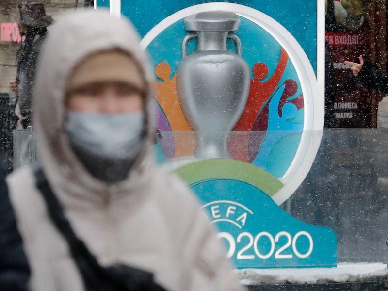 FILE PHOTO: A person wearing a protective face mask walks past the Euro 2020 countdown clock in central Saint Petersburg, Russia March 1, 2020. REUTERS/Anton Vaganov/File Photo