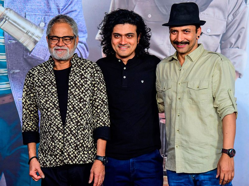 Bollywood actors Sanjay Mishra (L) and Deepak Dobriyal (R) along with film director Hardik Mehta pose for photographs as they attend the premiere of their Hindi drama film.