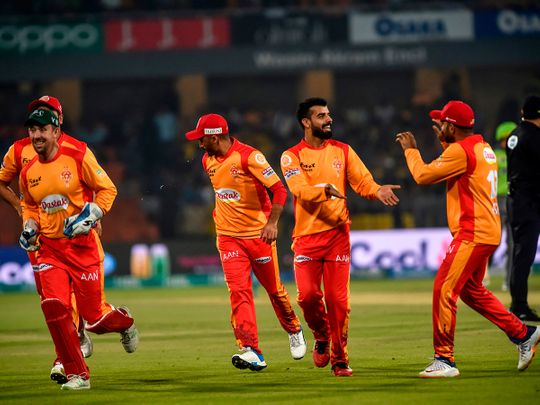 In this photo taken on March 4, 2020, Islamabad United's cricketers celebrate after the dismissal of Lahore Qalandars's Samit Patel during the Pakistan Super League (PSL) T20 cricket match between Lahore Qalandars and Islamabad United at the Gaddafi Cricket Stadium in Lahore.  / AFP / Arif ALI