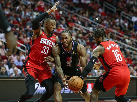 Los Angeles Clippers forward Kawhi Leonard attempts to control the ball as Houston Rockets forward Robert Covington (33) and guard Ben McLemore (16) defend