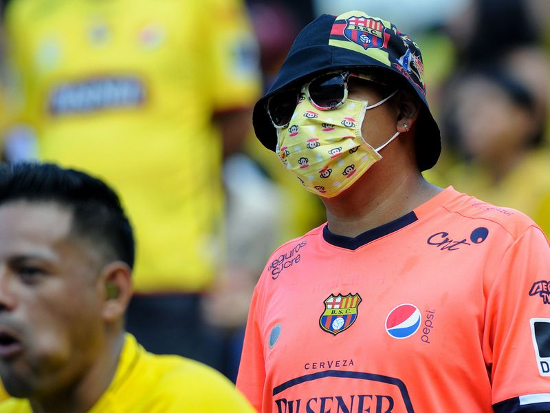 A football fan wears a protective mask as a preventive measure agaisnt the spread of the COVID-19 virus, during their Copa Libertadores football match, at the Monumental Stadium in Guayaquil, Ecuador, on March 4, 2020. / AFP / Jose ALVARADO