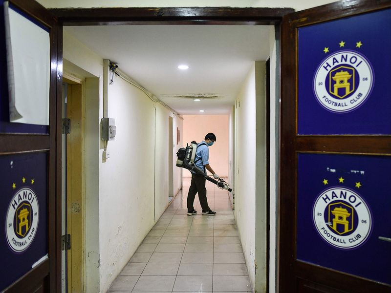 A health worker wearing a facemask sprays disinfectant inside the Hanoi Football Club team locker room, amid concerns of the spread of the COVID-19 novel coronavirus, at Hang Day stadium in Hanoi on March 6, 2020. / AFP / Manan VATSYAYANA
