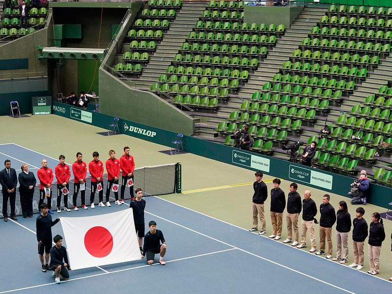Japanese tennis players, in red uniform, attend the opening ceremony of the Davis Cup qualifier between Japan and Ecuador, as it is held without spectators amid growing concern about the spread of a new coronavirus in Miki city, Hyogo prefecture, western Japan, Friday, March 6, 2020. (Nobuki Ito/Kyodo News via AP, File)