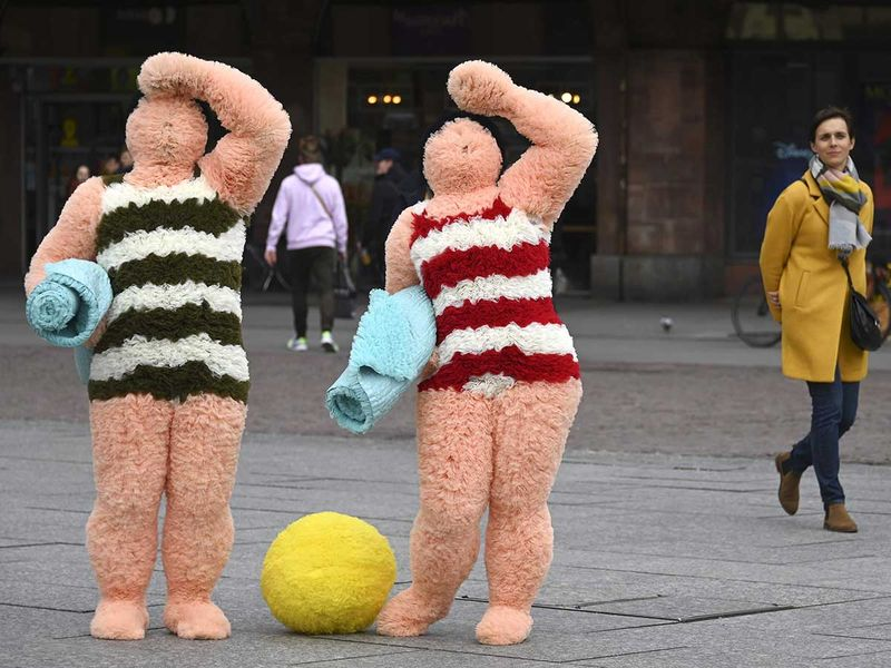 French artists Coco Petitpierre and Yvan Cledat, equipped with a beach ball and towels, perform a show entitled