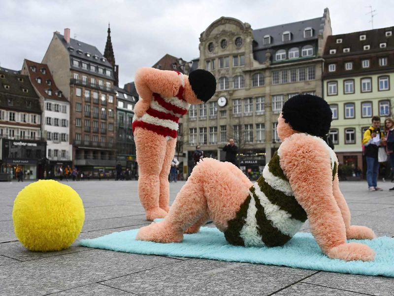 French artists Coco Petitpierre and Yvan Cledat, equipped with a beach ball and towels, take part in a creative performance called