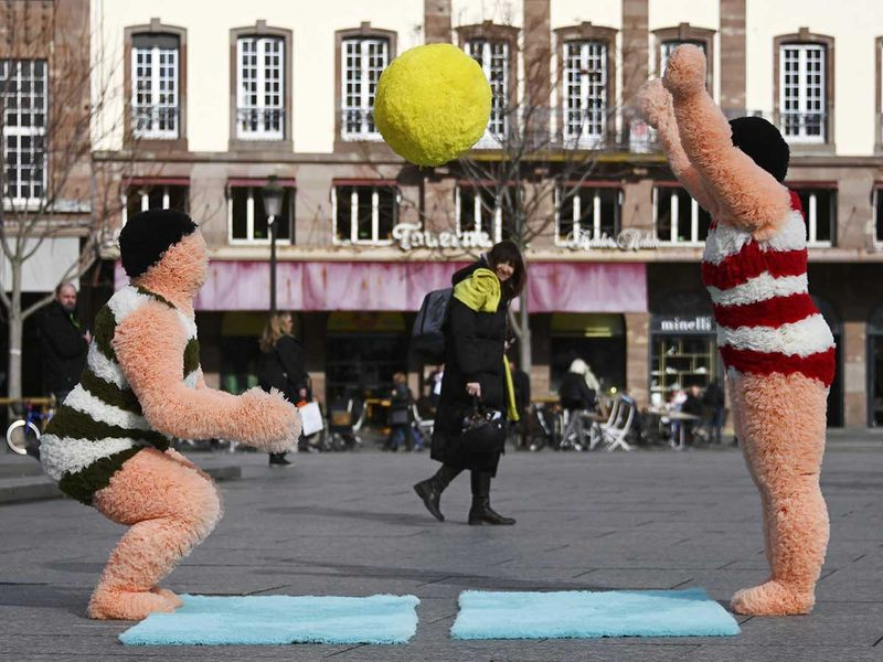 French artists Coco Petitpierre and Yvan Cledat, play with a beach ball during a creative performance called