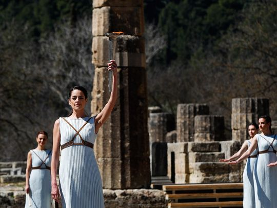 Greek actress Xanthi Georgiou, playing the role of the High Priestess, holds up the torch during the flame lighting ceremony at the closed Ancient Olympia site, birthplace of the ancient Olympics in southern Greece, Thursday, March 12, 2020. Greek Olympic officials are holding a pared-down flame-lighting ceremony for the Tokyo Games due to concerns over the spread of the coronavirus. Both Wednesday's dress rehearsal and Thursday's lighting ceremony are closed to the public, while organizers have slashed the number of officials from the International Olympic Committee and the Tokyo Organizing Committee, as well as journalists at the flame-lighting. (AP Photo/Thanassis Stavrakis)
