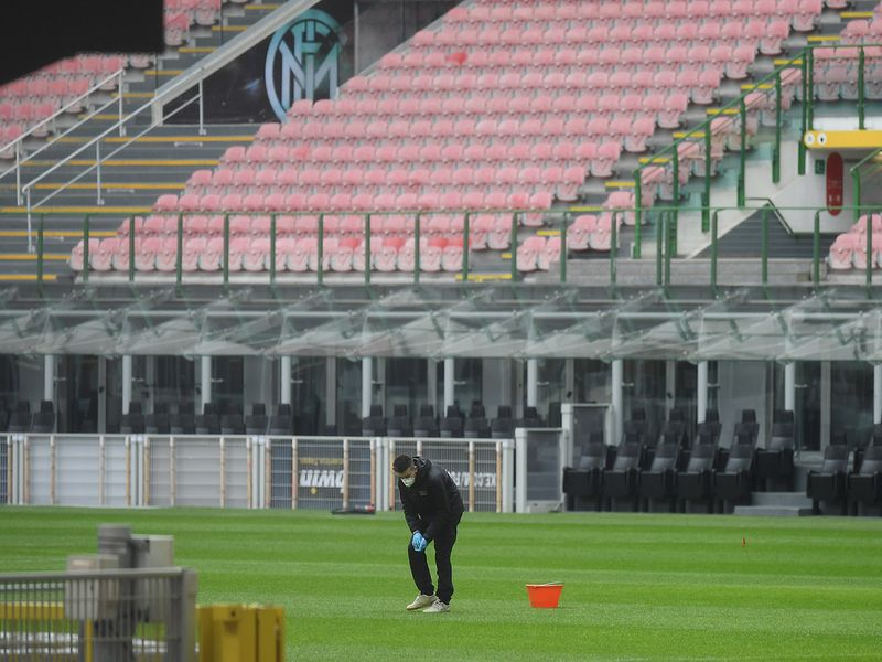 Inter Milan v Getafe Match Postponed - San Siro, Milan: A member of the groundstaff wearing a face mask and protective gloves on the pitch after the match is postponed