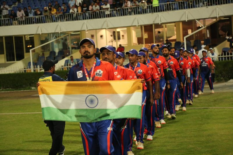 The Indian team walk into the Sharjah Stadium ground with their nation's flag.