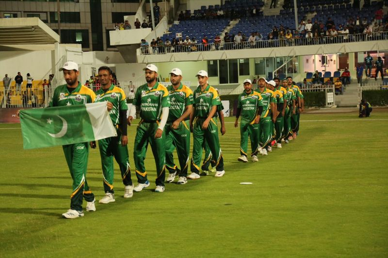 The Pakistan team walk into the Sharjah Stadium ground with their nation's flag.
