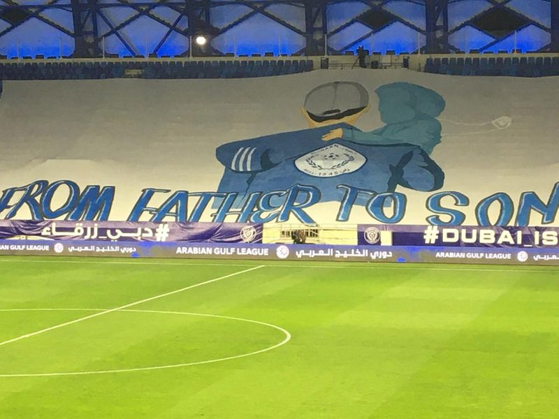 A large banner fills the empty stand at the match between Al Nasr and Khor Fakkan
