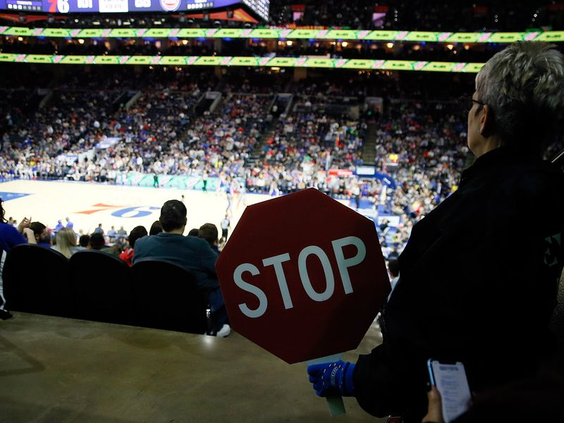 An usher at the Wells Fargo Center holds a Stop sign during an NBA basketball game between the Philadelphia 76ers and the Detroit Pistons, Wednesday, March 11, 2020, in Philadelphia. (AP Photo/Matt Slocum)