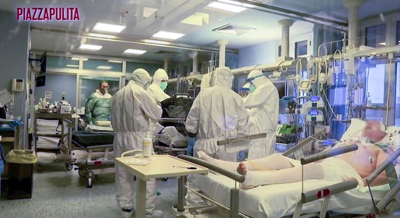Medical staff in protective suits treat coronavirus patients in an intensive care unit at the Cremona hospital in northern Italy.