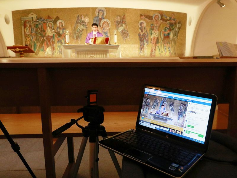A priest celebrates mass live-streamed on Facebook following the suspension of mass gatherings due to the coronavirus outbreak, at an almost-empty chapel in Manila Cathedral in Manila, Philippines