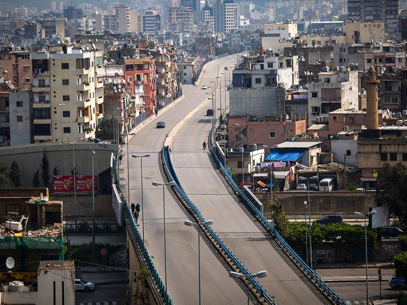 People walk on a highway that is almost empty of cars, east Beirut.