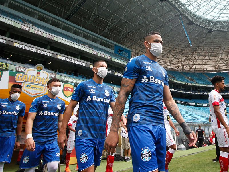 Players of Gremio enter the field wearing protective face masks to prevent the spread of the new Coronavirus, before the match against Sao Luiz
