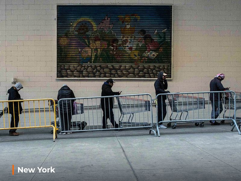 Customers make a line with shopping carts at a local retail store, March 16, 2020 in New York.