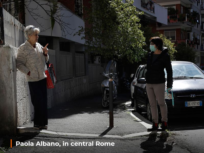 Enza Garzia, 79, left, talks at a distance with Paola Albano, in central Rome