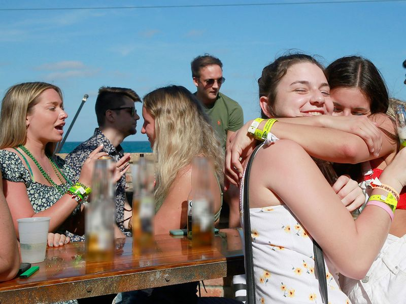 Laura Haverty, left, and Haley Halse, both of Saratoga, N.Y., hug at McSorley's Beach Pub, in Fort Lauderdale Florida