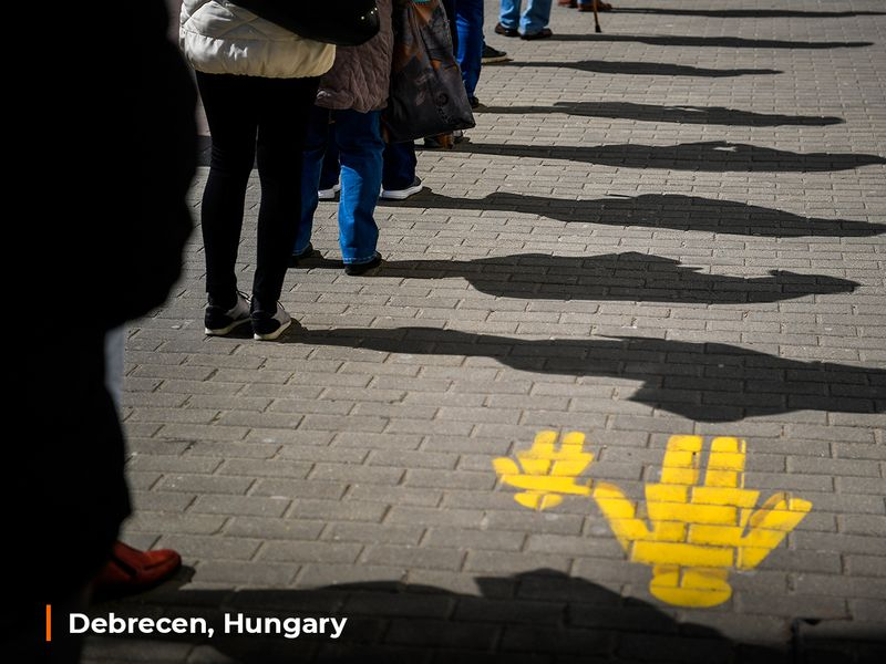 People keep their distance as they queue up in front of a post office in Debrecen, Hungary