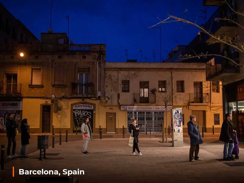 People line up to enter a shop to buy supplies in Barcelona, Spain