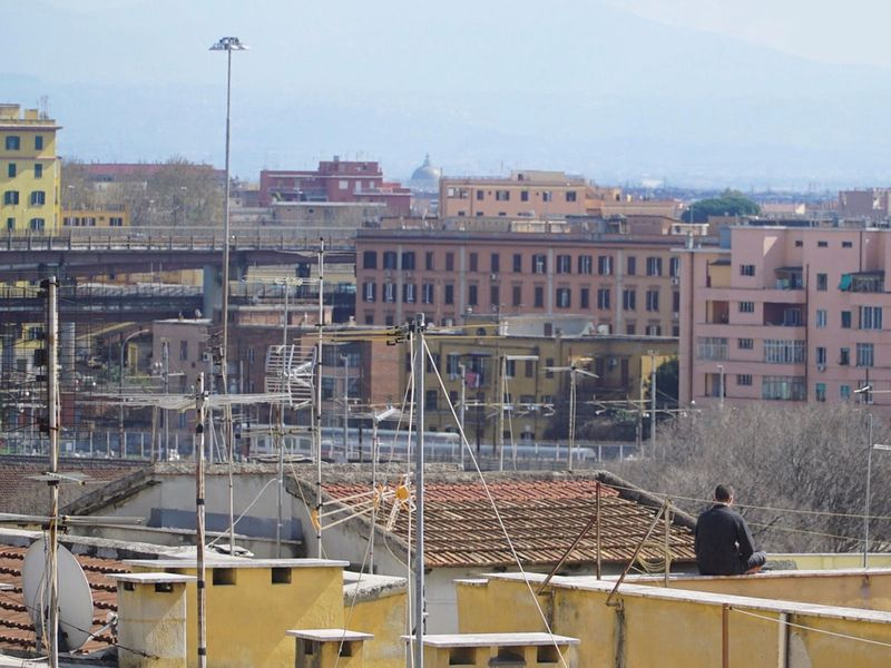 A man sits alone on a roof terrace during Italy's nationwide lockdown in Rome