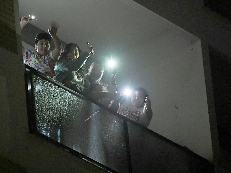 People light their smart phones on a balcony as part of nationwide flash mob to