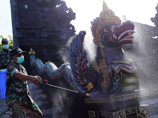Indonesian soldiers spray disinfectant on a statue to prevent the spread of coronavirus disease (COVID-19) at Tanah Lot temple in Tabanan, Bali, Indonesia, March 20, 2020.