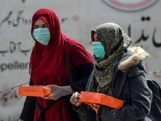 Women wearing facemasks as a preventive measure against the spread of the COVID-19 coronavirus walk along a street in Rawalpindi on March 13, 2020.