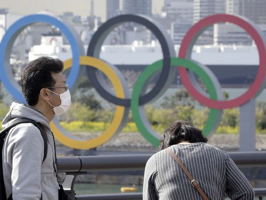A man wearing a protective mask stands in front of Olympic rings in Tokyo