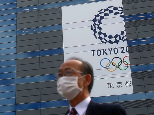 A man wears a protective mask in front of a banner for the upcoming Tokyo 2020 Olympics.