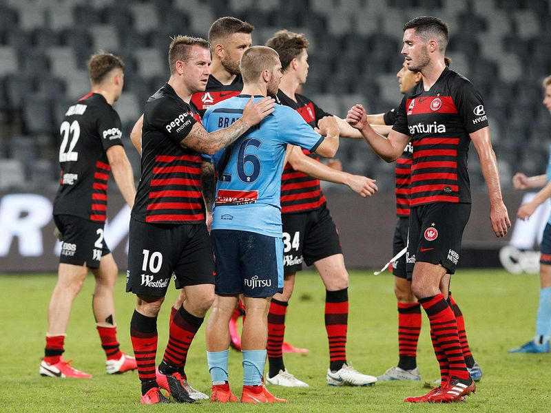 Players fist-bump in an empty Bankwest Stadium, shuttered from fans due to the COVID-19 coronavirus outbreak, at the end of the A-League match between Sydney and Western Sydney Wanderers