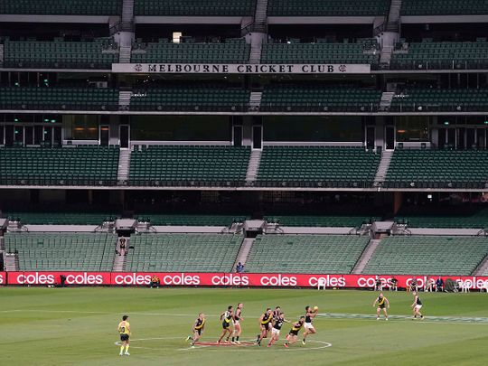 Players from Richmond and Carlton play their Australian Rules Football league game at a empty Melbourne Cricket Ground in Melbourne, Thursday, March 19