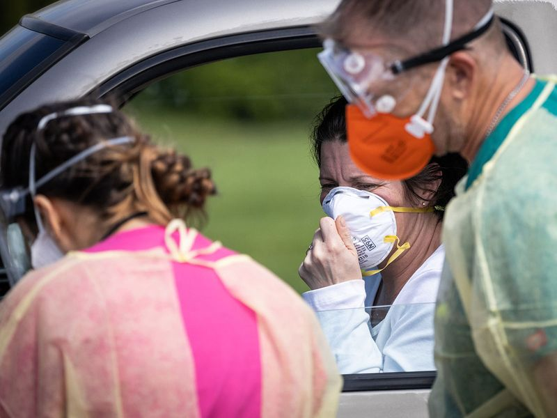 Nurses examine a patient at a drive-through coronavirus testing facility in Yuba City, California.