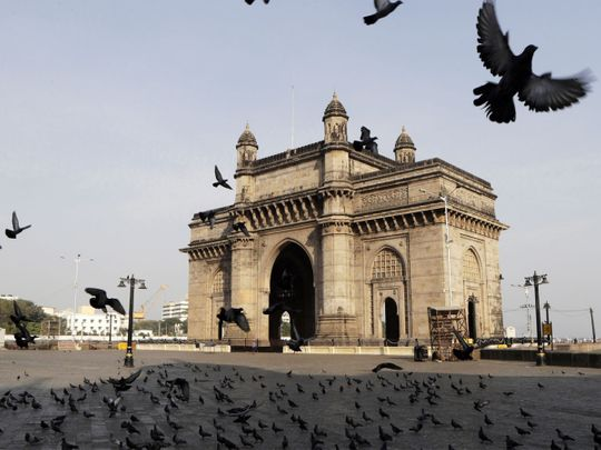 Pigeons fly at a deserted Gateway of India monument in Mumbai