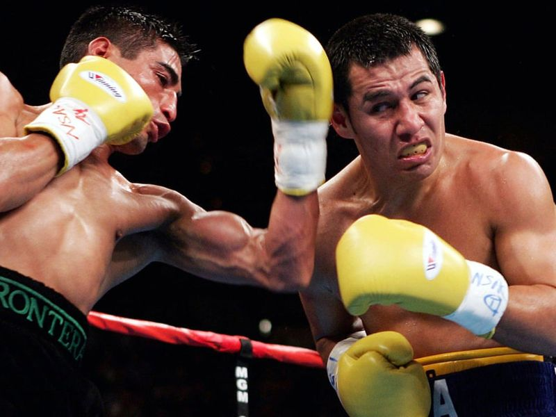 Erik Morales throws a glancing blow to the head of Marco Antonio Barrera during their third fight, in 2004.