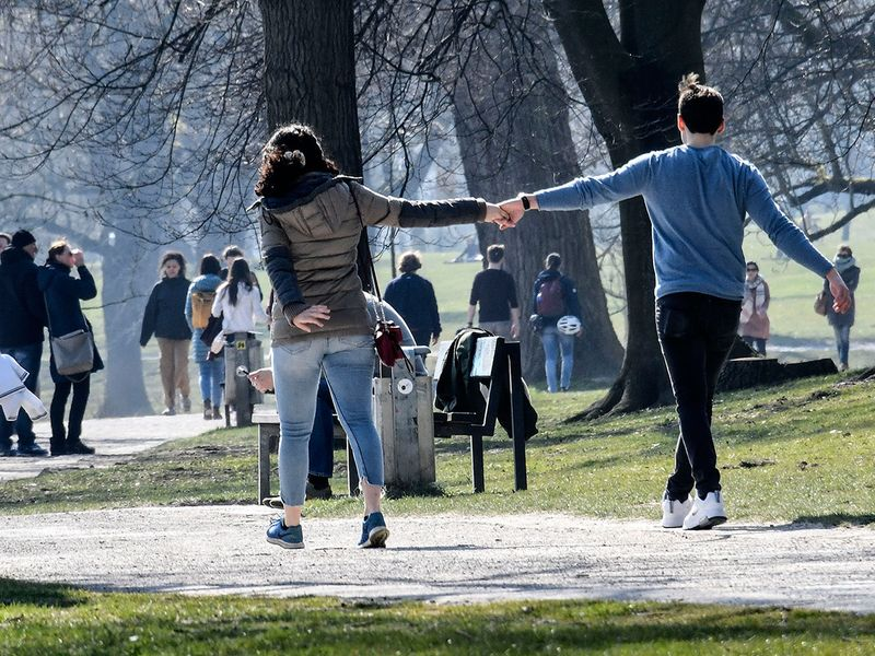 A couple hold hands as most people observe social distancing due to the virus outbreak on a sunny day in Muenster, western Germany. The German government has considerably restricted public life and allowed only two non-family members together in public.