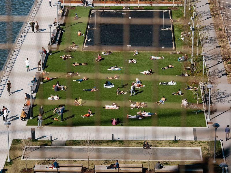 People enjoy sunny weather at New York's Domino Park on Friday, amid the coronavirus pandemic. The mayor is threatening to fine residents who flout the social-distancing rules.