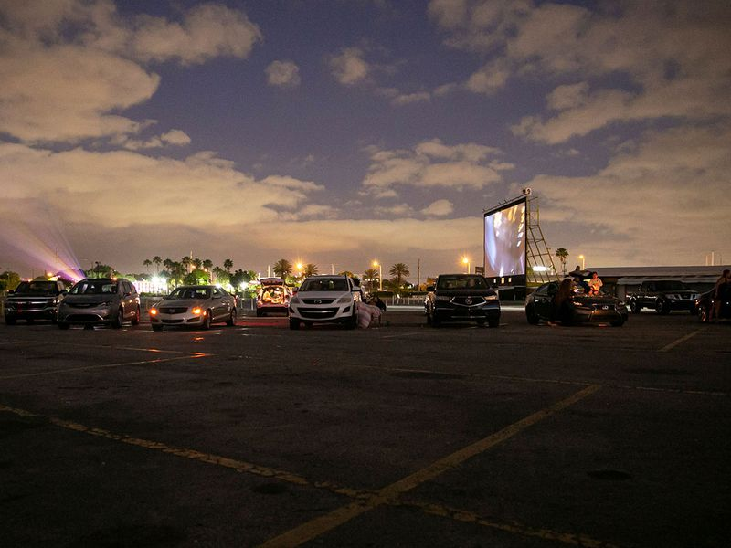 People in their cars watch a movie at a drive-in theatre while keeping social distancing following the outbreak of COVID-19 in Fort Lauderdale, Florida, U.S.