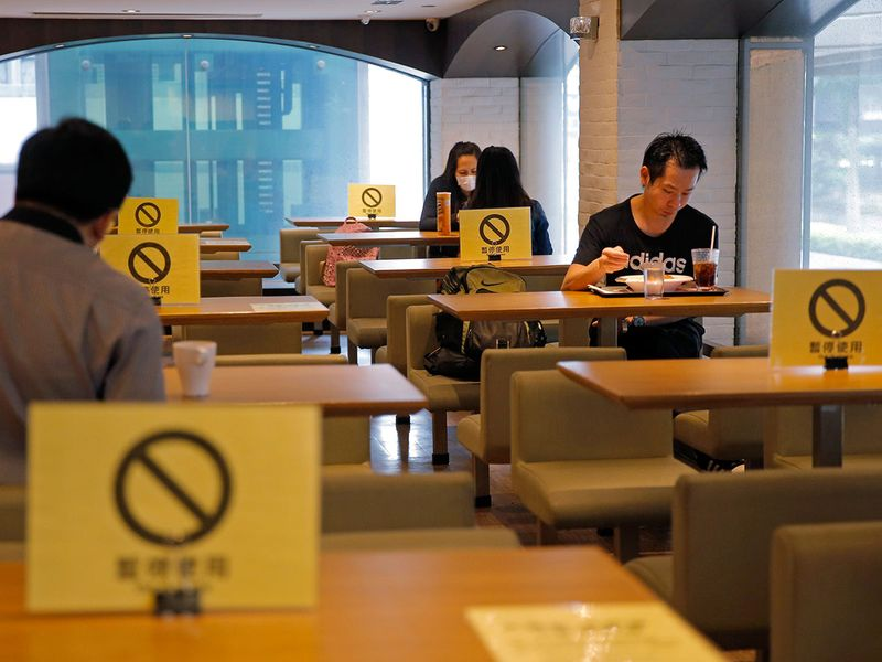 Social distancing signs are seen on tables at a restaurant in Hong Kong.