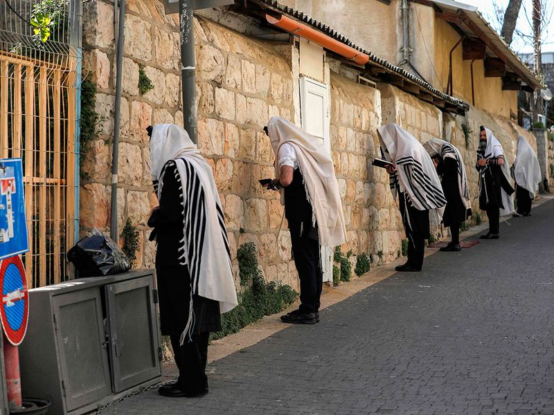 Ultra-Orthodox Jews, wearing the traditional Tallit Jewish prayer shawls, pray along a street outside their closed synagogue following instructions to stop the spread of the COVID-19 pandemic while keeping a distance of two meters from one another, in Je