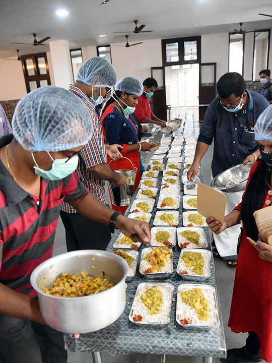 Volunteers preparing food packets in a community kitchen to distribute among the needy during the nationwide lockdown in Kochi.
