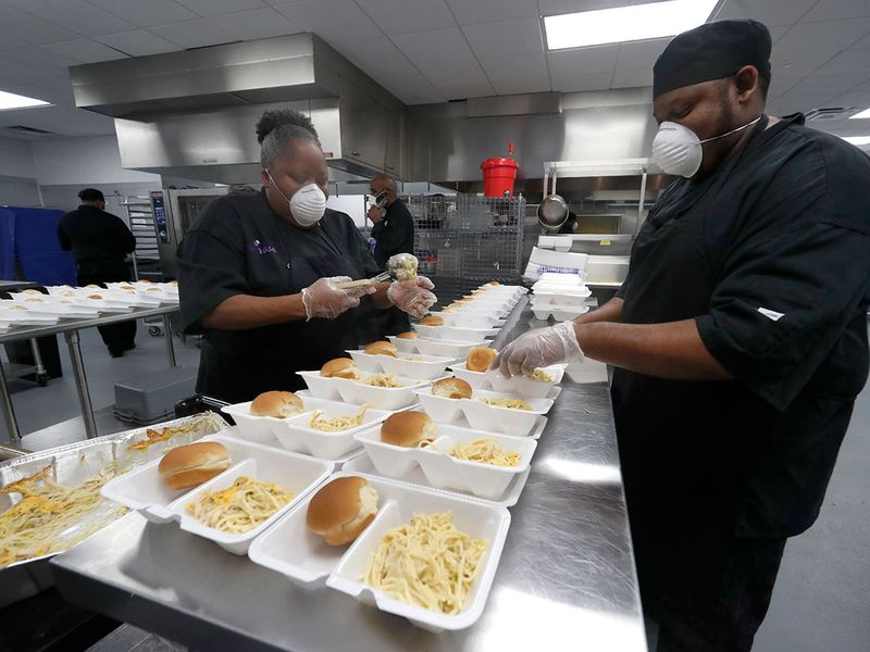 Chefs Rose Barrett, left, and her son James assemble plates of chicken tetrazzini being made by the staff in the commercial kitchen at The Potters House Church in Dallas.