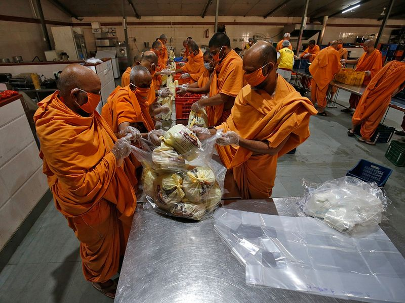 Members of Bochasanwasi Akshar Purushottam Sanstha (BAPS) pack vegetables inside a community kitchen to be distributed amongst poor people during a 21-day nationwide lockdown to limit the spreading of COVID-19 in Ahmedabad, India.