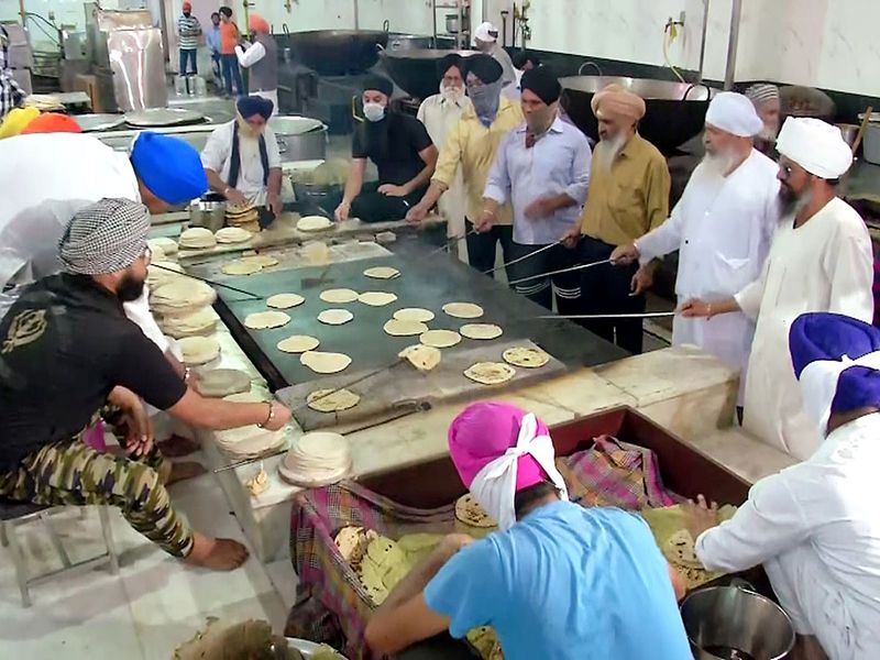 Sikh volunteers preparing food in the community kitchen to distribute it among the needy during the nationwide lockdown at Bangla Sahib Gurudwara in New Delhi.