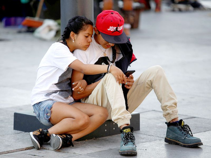 A couple looks at a mobile phone, in Mexico City