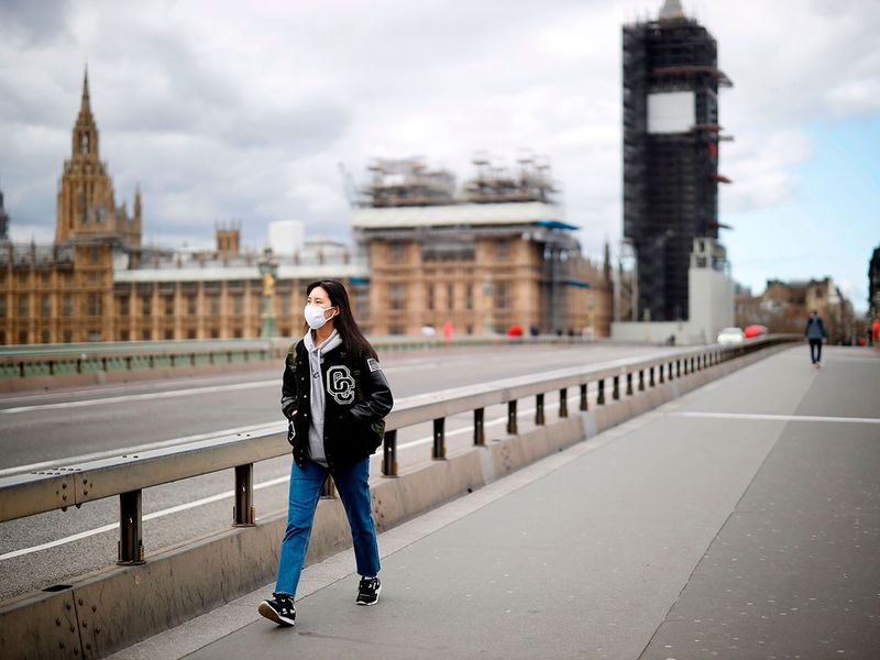 A woman wearing a face mask as a precautionary measure against COVID-19, walks across Westminster Bridge in London, as life in Britain continues during the nationwide lockdown to combat the novel coronavirus COVID-19 pandemic.