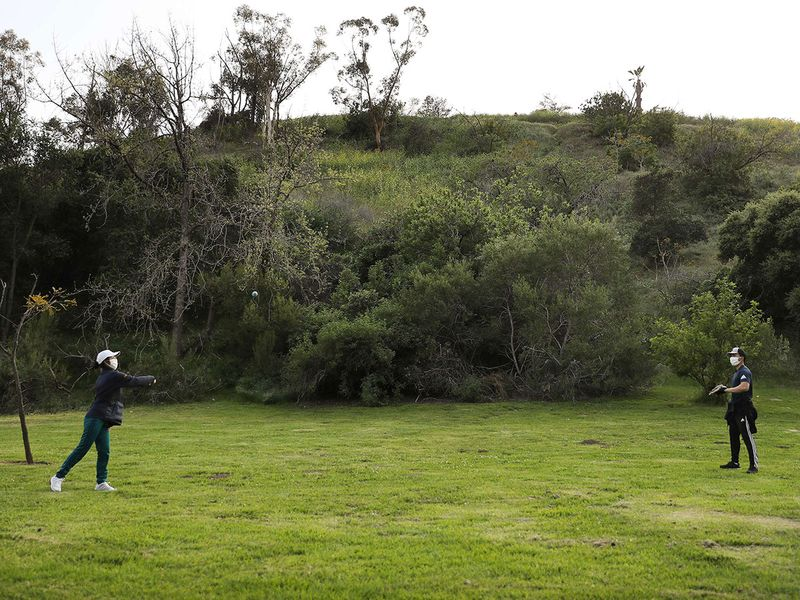 People play catch wearing face masks in Elysian Park amid the coronavirus pandemic in Los Angeles, California. The U.S. COVID-19 death toll has now surpassed 8,000.