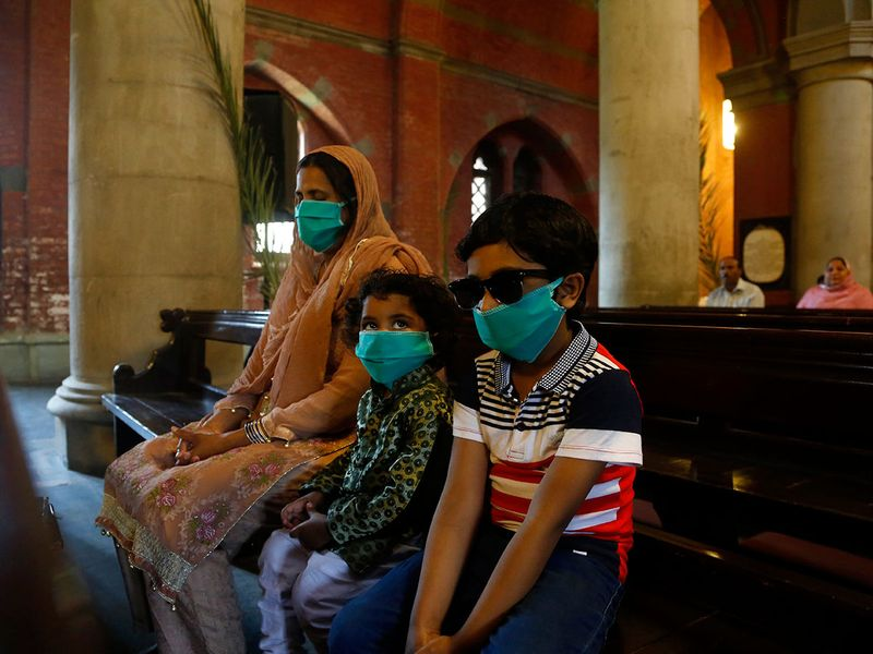 A Christian family wearing face masks as a precaution against coronavirus attend Palm Sunday service at a nearly-empty church due to a government imposed lockdown to help stop the spread of the virus, in Lahore, Pakistan.