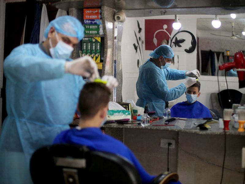 A Palestinian barber, wearing a face mask and a protective suit as a precaution against the coronavirus disease, cuts the hair of a customer in Rafah in the southern Gaza Strip.